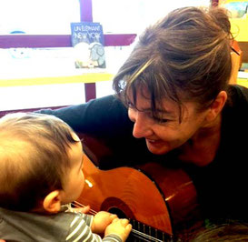 Bébé jouant de la guitare lors d'un atelier d'éveil musical avec Stéphanie Bourgeois Lang.