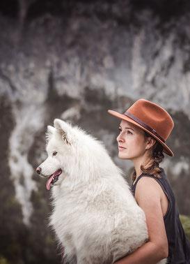 Mädchen mit rostrotem Fedora Hut hält einen weissen Samojeden Schlittenhund im Arm vor einer Berg Kulisse fotografiert von der Ostschweizer Hunde Monkeyjolie