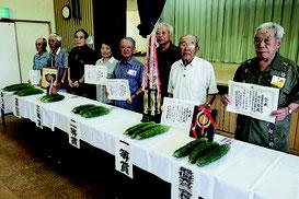 ゴーヤ品評会で最優秀賞を受賞した内原さん(右端)ら入賞者=12日午前、老人福祉センター