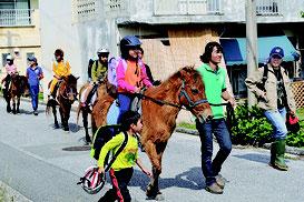 昔の移動手段を体験しようと、ヨナグニ馬に乗って楽しむ子どもたち=久部良