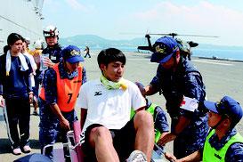 甲板から海上自衛官らが患者役を担架などで運んだ。「いせ」は2013年に台風30号被害の救援でフィリピン沖に派遣された。後方は患者を空輸した陸自ヘリ=2日、恩納村沖