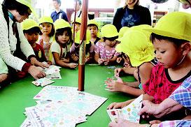 上原館長(左)と専用用紙を使って紙コップを作る園児ら=9日、那覇市あけぼの公園