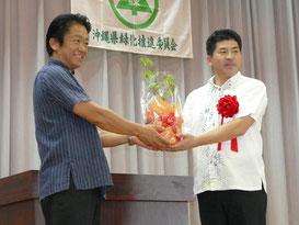次期開催地、宜野座村の當眞村長に中山市長が苗木を贈呈した=20日午前、八島小