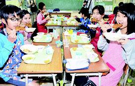 特製かき揚げを食べる児童たち=10日、石垣小学校