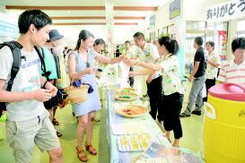 2016年8月1日、観光の日キャンペーンでパインを試食する観光客=石垣港離島ターミナル