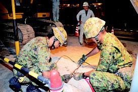 大川のゆいロードで不発弾が発見され、調査する自衛隊員=4日夜、市内大川