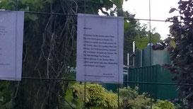 Zu sehen sind Textblätter an einem Baugitter im Park.
