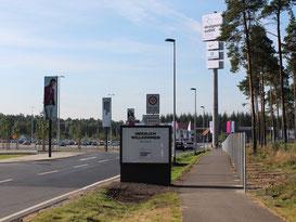Ansicht auf die mit Werbefahnen gesäumte Zufahrtsstraße zum Designer Outlet Soltau