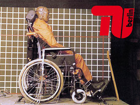 Crash-test dummy sits in a wheelchair, which is secured with a 4-point retractor restraint system