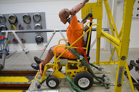 Crash-test dummy sits in a powered wheelchair on a sled. Wheelchair and dummy are secured with heavy duty restraint system.