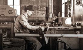 Employee sits in a production hall and works on a machine to manufacture agricultural machinery