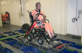 Crash-test dummy sits in a power wheelchair, which is secured on a sled