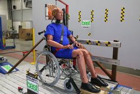 Crash-test dummy sits in a folding wheelchair on a sled. Wheelchair and dummy are secured with Protektor restraint system and head & backrest FutureSafe