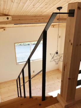 木製スケルトン階段と星型ペンダント照明とフラットバー手摺