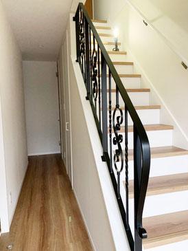 玄関吹き抜け階段に取り付いた、唐草模様が豪華なアイアン手すり