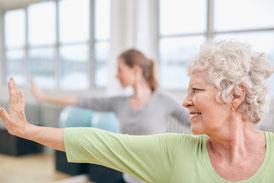 Zwei Frauen machen parallel zueinander eine Yogaübung. Beide strecken den Arm nach vorne aus. Die Hand ist senkrecht zum Körper aufgestellt. Yoga Personal Training in Waldenbuch, Raum Böblingen