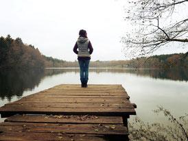 Frau steht gedankenverloren am Steg und schaut auf das Wasser.