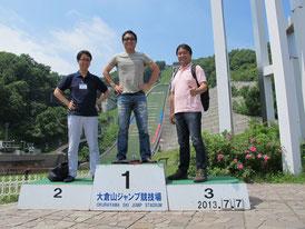 大倉山ジャンプ場の表彰台に登って記念写真を取る参加者の方々