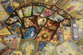 Cartes du tarot étalées en éventail et d'autres jeux très colorés remplissent l'image