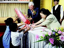 親族から花束を受け取る石垣繁さん=11日夜、市内ホテル