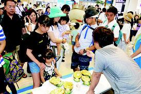 石垣空港で特産品のパインを試食する観光客=2016年8月