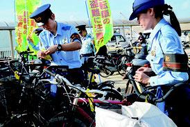 自転車に札を貼り付ける署員=16日、離島ターミナル