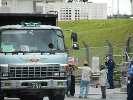 工事車両の近くで、プラカードを手に通行を妨害する基地反対派=8日午後、米軍キャンプ・シュワブ前