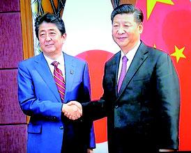 首脳会談で握手する習主席と安倍首相=中国国営テレビより