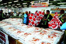 新米の販売開始セレモニーで、米袋の上にかけられた布が取り払われた=8日午前、ゆらてぃく市場