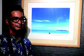 ▲大賞に輝いた高江洲さんと作品「君に見せたい海がある」 =21日夜、市内飲食店