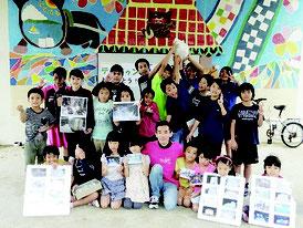 竹富小学校に雪を届けた川原さん(中央)と大喜びの児童たち=22日、竹富小中学校