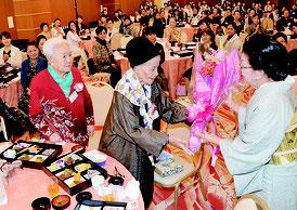 八重山の踊りの普及を務めた先輩たちに花束が贈呈された=27日、市内ホテル