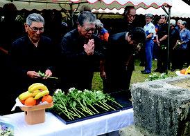 慰霊の塔前で献花して手を合わせる参列者たち=24日、宮良タフナー原