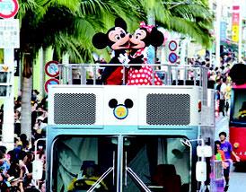 ミッキーらは軽快なリズムのテーマ曲を流しながら国際通りをパレードした=7日、国際通り