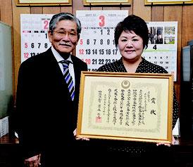 県知事賞を受賞した浦内さん(右)が我喜屋会長に受賞を報告した=11日、石垣市商工会館