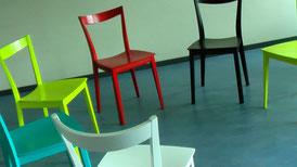 Stuhlkreis mit bunten Stühlen