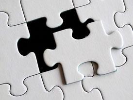 weißes Puzzle, ein Teil ist teilweise herausgelöst und man sieht den schwarzen Untergrund