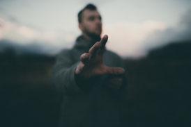 Unsicherer Mann mit ausgestreckter Hand