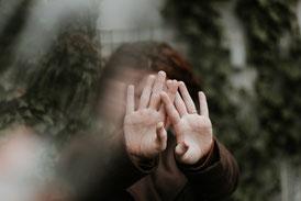 Frau mit ausgestreckten Händen vor ihrem Gesicht