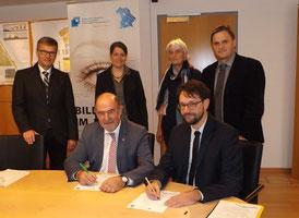 Landrat Willibald Gailler unterzeichnet, im Beisein der Geschäftsführer der Regina GmbH, Werner Brandenburger und Michael Gottschalk, Kooperationsvereinbarung mit Transferagentur Bayern