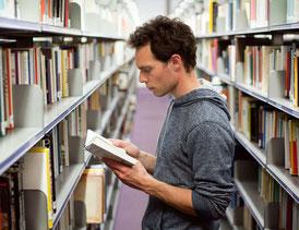 student mit buch in bibliothek