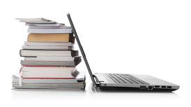 Ein Stapel Bücher und ein aufgeklappter Laptop