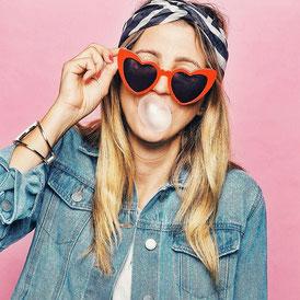 Julia, Bloggerin, Instagram Influencerin und zukünftige Autorin mit Tuch auf dem Kopf, Sonnenbrille und einer Kaugummiblase im Mund. der Hintergrund  ist rosa und sie trägt eine blaue Jeansjacke