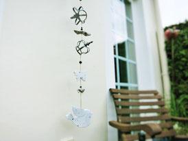 Deko Kette mit weißem Holzvogel - Metallkronen und Treibholz auf der Terrasse neben einem Holzstuhl aufgehängt.
