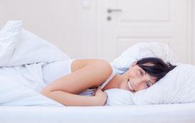 Versandreinigungmueden.de, Inselreinigung, Bettartikel, Bild zeigt Frau in weißer Bettwäsche
