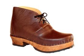 Modèle de bottines pour homme inspiré par les classiques sabots suédois, sur semelle noyer et cuir marron. le tige monte juste au-dessus de la cheville.