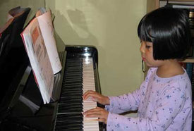 girl learning the piano