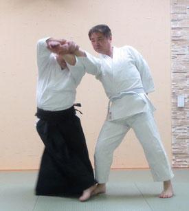 画像①b 四方投げの持ち方で振りかぶり額に手背を結ぶことで前方の足先を外股で踏み、前方回転の軸足とする。