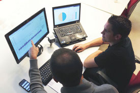 Fachleute bei der Auswertung am Computer von Schwingungsmessdaten des Systems Wi-care (Schwingungsdiagnose)