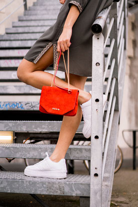 Sneakers blanches, sac rouge et robe kaki pour un style weekend